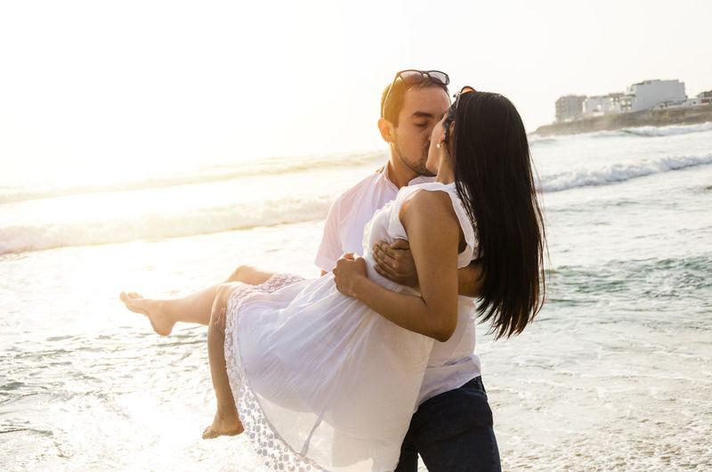 Couple kissing at beach against clear sky