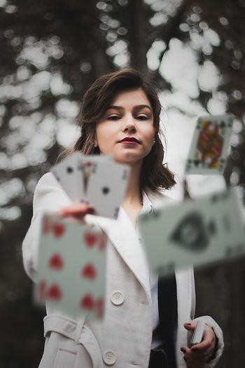 Portrait of woman throwing cards