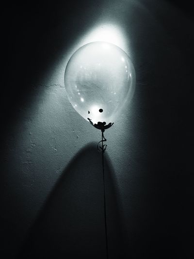 Low angle view of light bulb against wall