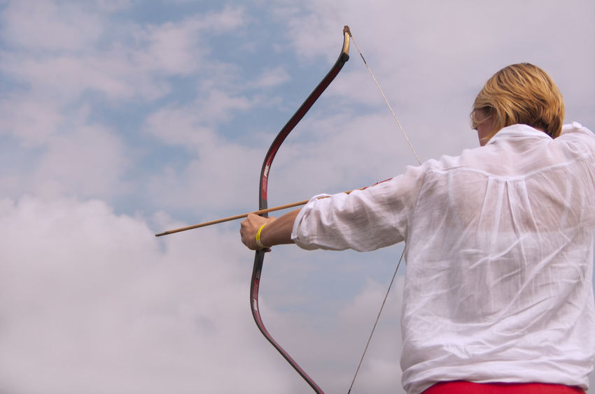 girl shoots a bow Gunslinger  Sky Accuracy Purposefulness Sharpshooter Target Aim Bow And Arrow Bow, Arrow Bowling Cloud - Sky Day Direction Hit Hitchhiking Holding Marksman One Person Real People Rear View Shooter Mag Skill  Sky Sports Race Waist Up