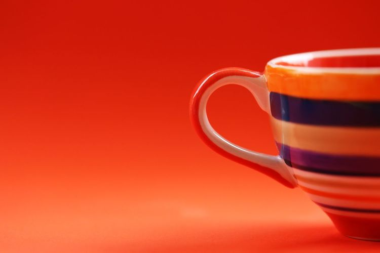Close-up of coffee cup against red background