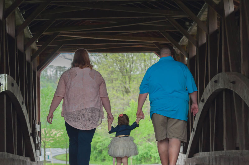 Family Walking Together Under a Covered Bridge Family Husband Relationship Woman Architecture Bonding Built Structure Child Covered Bridge Daughter Full Length Girl Leisure Activity Lifestyles Love Mammal Outdoors People Real People Rear View Standing Togetherness Walking Wife