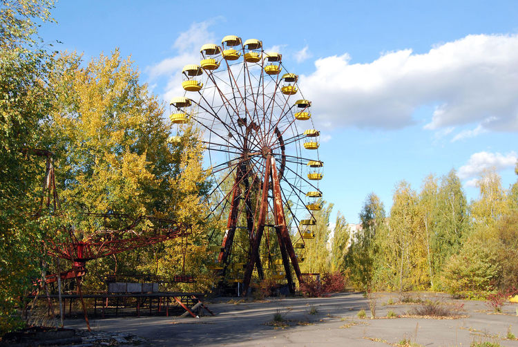 Ferris wheel by road against sky during autumn