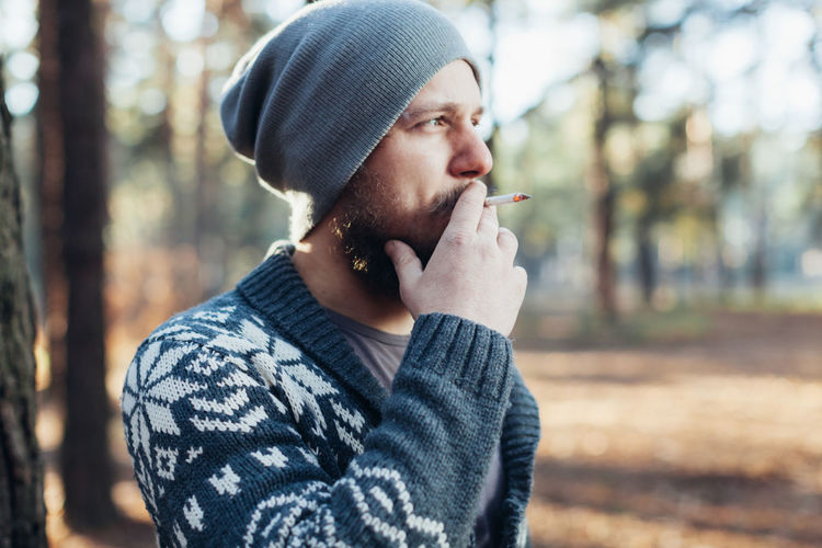 Man smoking cigarette in forest