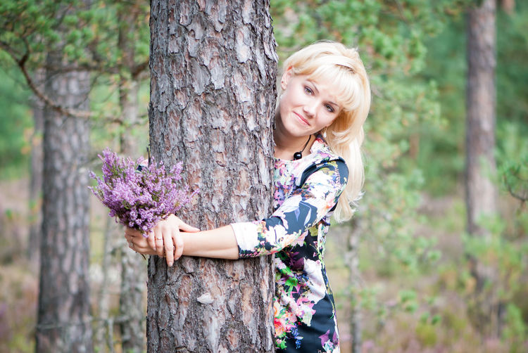 Portrait of happy young woman standing against tree trunk