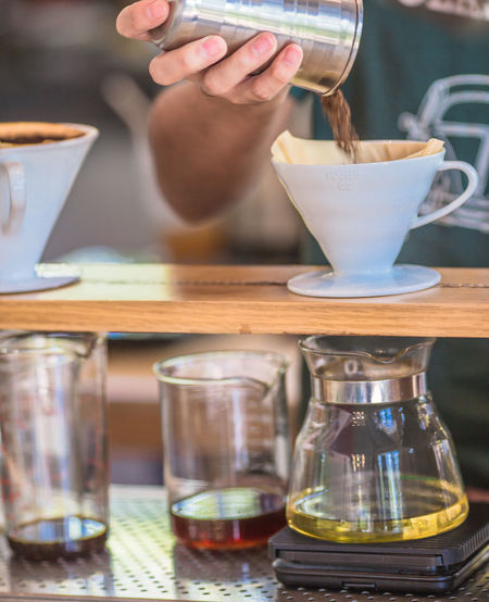 Midsection of man making coffee in cafe