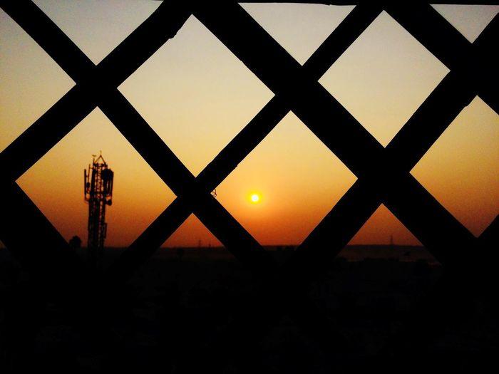 Silhouette fence against orange sky