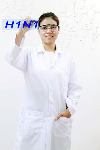 Portrait Of Doctor Writing H1N1 While Standing Against White Background