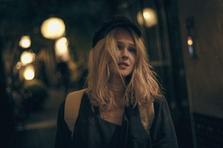 Portrait of woman against illuminated street at night