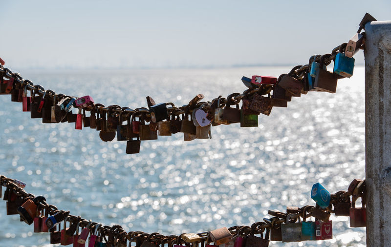 Close-up of love locks hanging on chain against sea