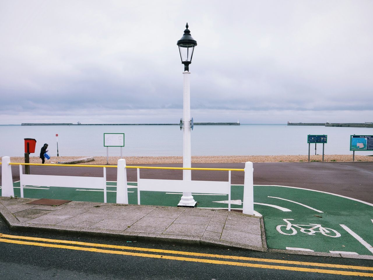 Street light by bicycle lane at beach against cloudy sky