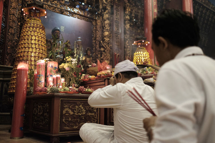 Benoa, Bali, Indonesia - January 28, 2017 : People praying and wishing a happy chinese new year on vihara satya dharma. Adult Architecture Belief Built Structure Clothing Illuminated Indoors  Lifestyles Men People Place Of Worship Praying Real People Rear View Religion Spirituality Waist Up Women