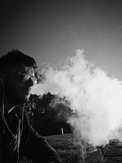 Man smoking against clear sky