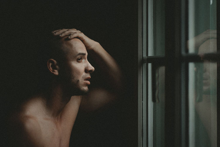Close-up of depressed man looking through window at home