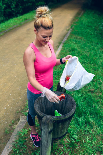 Smiling Woman Throwing Garbage In Can