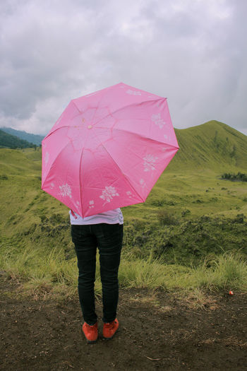 Women holding pink umbrella with green peak background Pink Umbrella Nature Standing EyeEm Best Shots EyeEm Nature Lover Sky Cinematic EyeEm Selects Canonphotography Umbrella Protection One Person Security Rain Standing Holding Nature Women Pink Color Wet Full Length Plant Day Adult Cloud - Sky Rear View Leisure Activity Outdoors