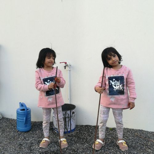 Twins standing against white wall