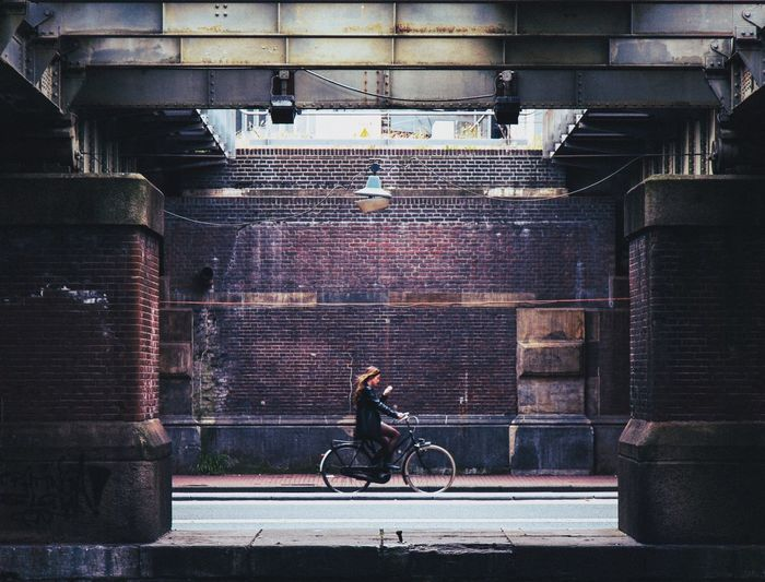 Man riding bicycle on street against building in city