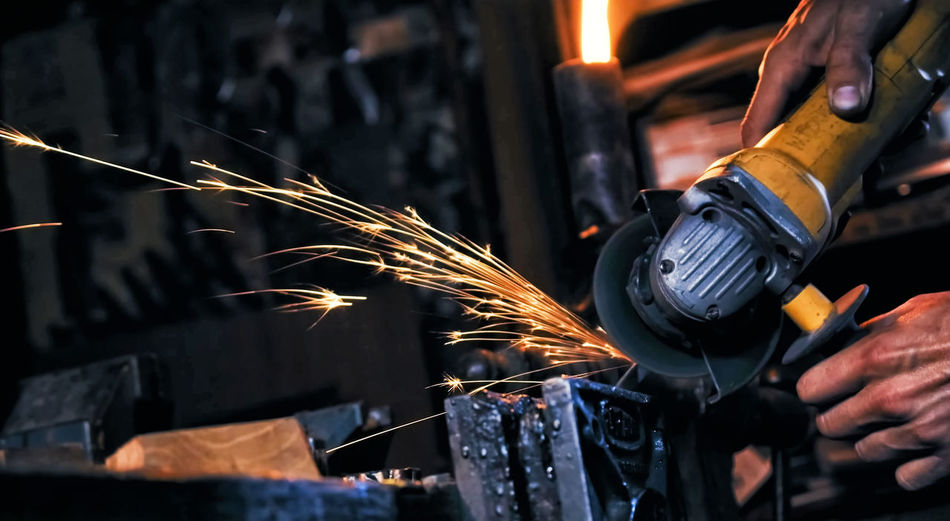 Cropped Hands Of Male Worker Cutting Metal In Workshop