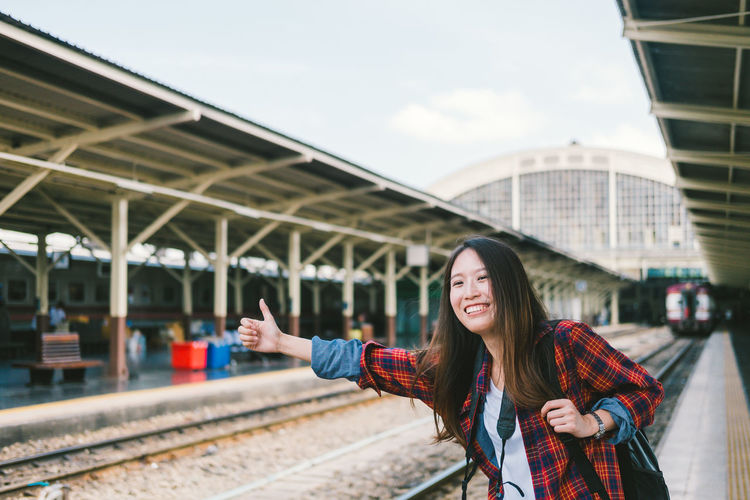 Portrait of smiling young woman standing on railroad station platform
