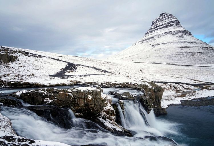 Scenic view of waterfall against snow covered mountain and sky during winter
