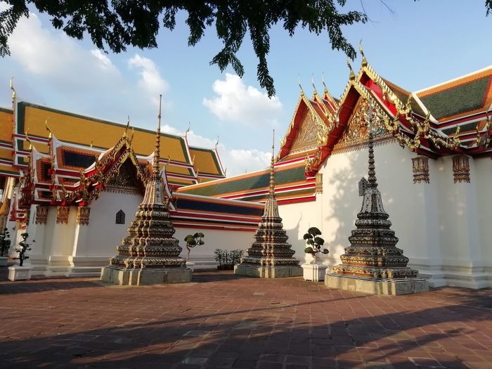 Traditional temple by building against sky