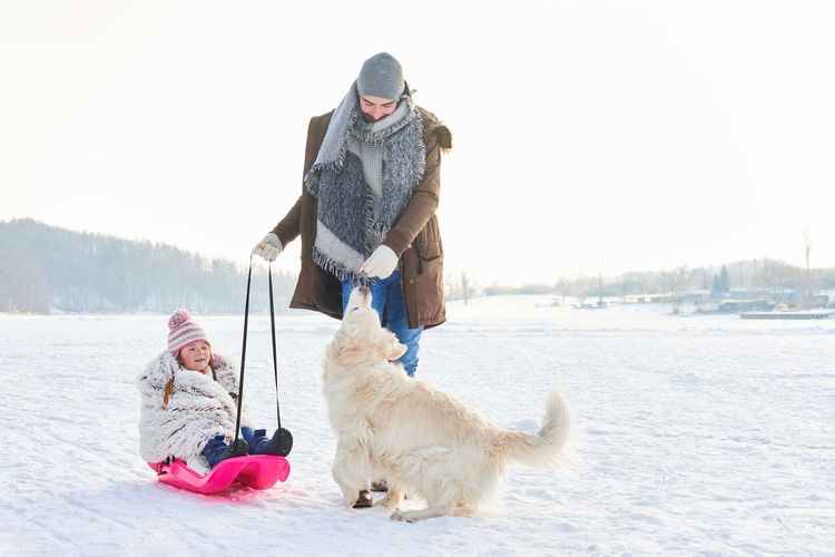 Father and daughter feeding dog during winter