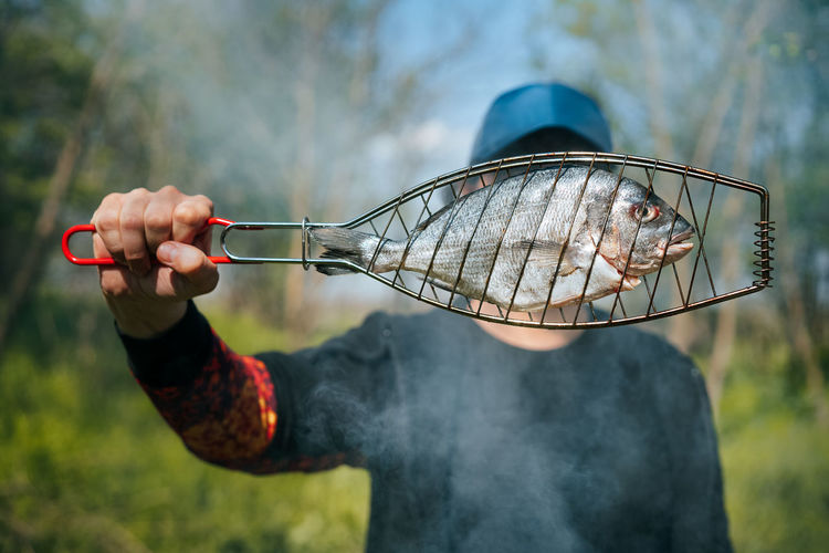 Man holding raw fish for grill