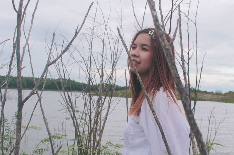 Close-up of smiling young woman standing at river against sky