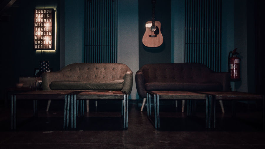 Empty sofas and tables against guitar on wall