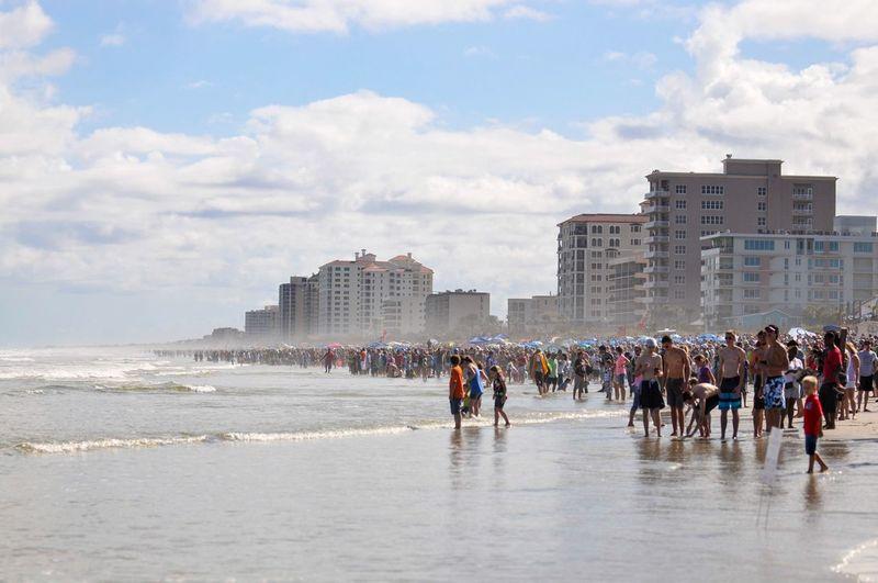 People enjoying at beach by buildings against sky