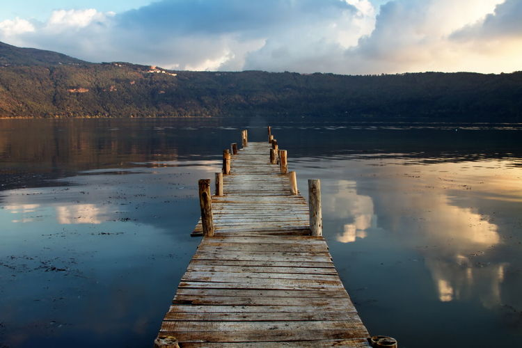 Wooden Jetty Over Lake By Mountains Against Cloudy Sky