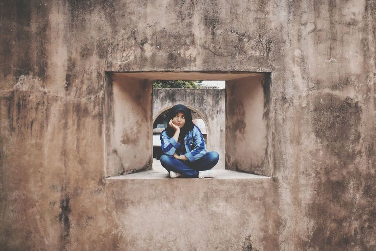 Woman sitting on window of abandoned building