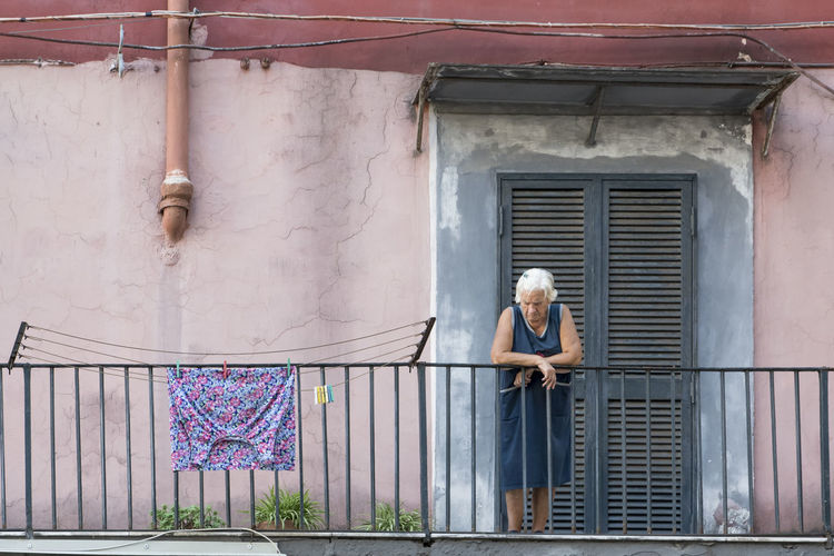 Woman standing by window of building