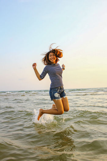 Full Length Of Happy Woman Jumping In Sea Against Sky