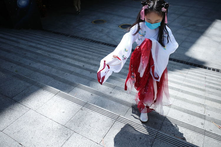 High angle view of girl in traditional chinese clothes standing on zebra crossing
