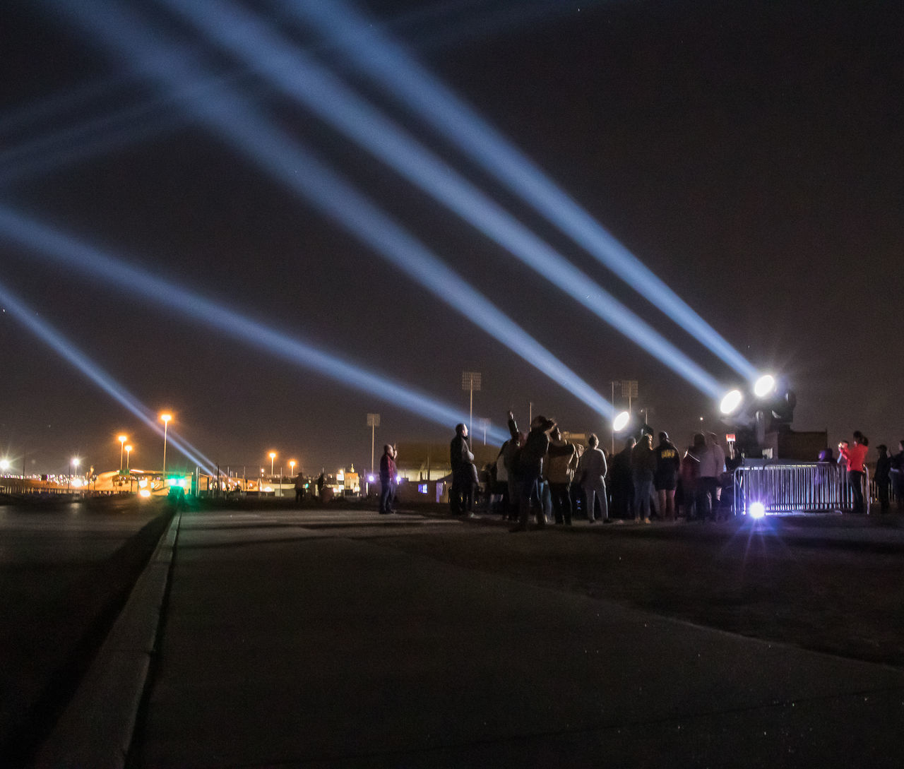 night, illuminated, transportation, large group of people, crowd, group of people, lighting equipment, real people, city, street, architecture, road, light - natural phenomenon, light beam, sky, mode of transportation, built structure, nature, arts culture and entertainment, outdoors, light, nightlife