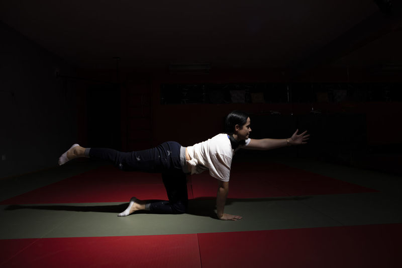 Portugal; Aula de Yoga Yogagirl Yoga Poses Full Length One Person Sport Young Adult Human Arm Limb Strength Indoors  Sports Clothing Red Clothing Flexibility Young Men Arms Outstretched Adult Casual Clothing Healthy Lifestyle Practicing Skill  Arms Raised Human Limb Black Background