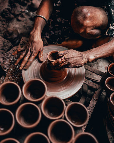 Midsection of person working on pottery wheel