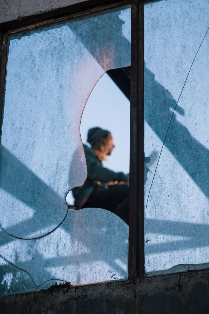 Low angle view of woman sitting against sky seen through window