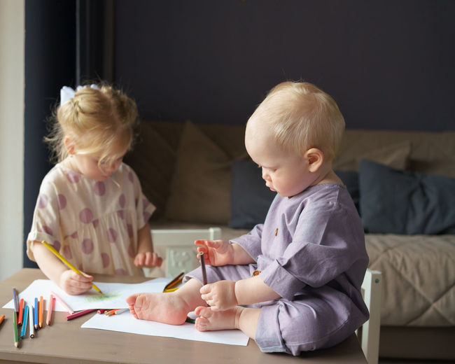 Two kids brother and sister drawing and playing together at home