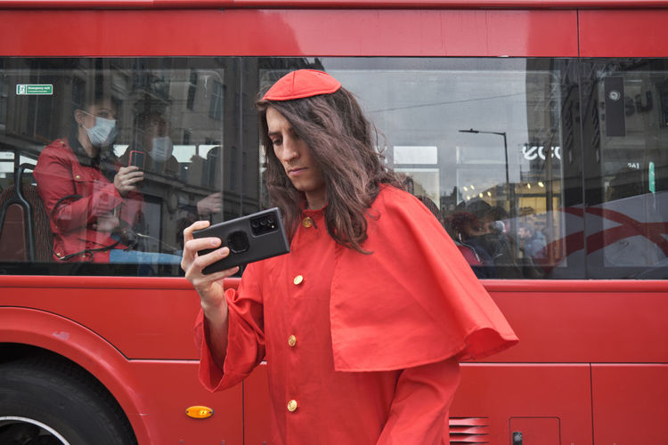 Full length of woman photographing with mobile phone while standing in city