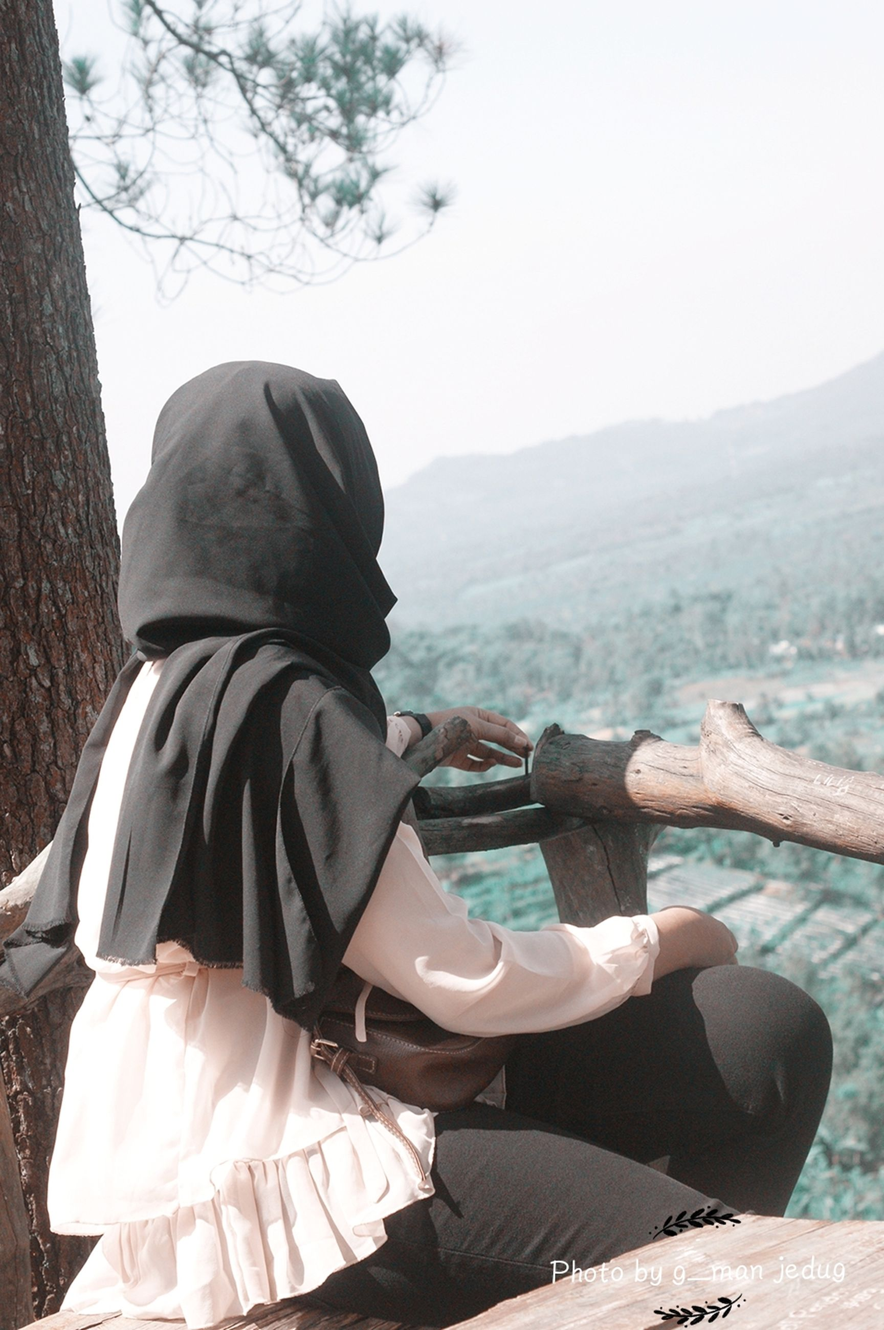 real people, one person, lifestyles, nature, day, tree, leisure activity, clothing, beauty in nature, non-urban scene, sky, plant, sitting, focus on foreground, adult, outdoors, women, mountain, scenics - nature, looking at view, hood - clothing