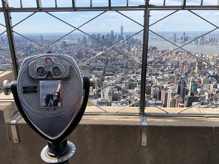Close-up of coin-operated binoculars against cityscape and sky
