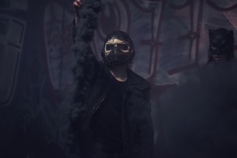 Man in mask holding distress flare while standing against wall