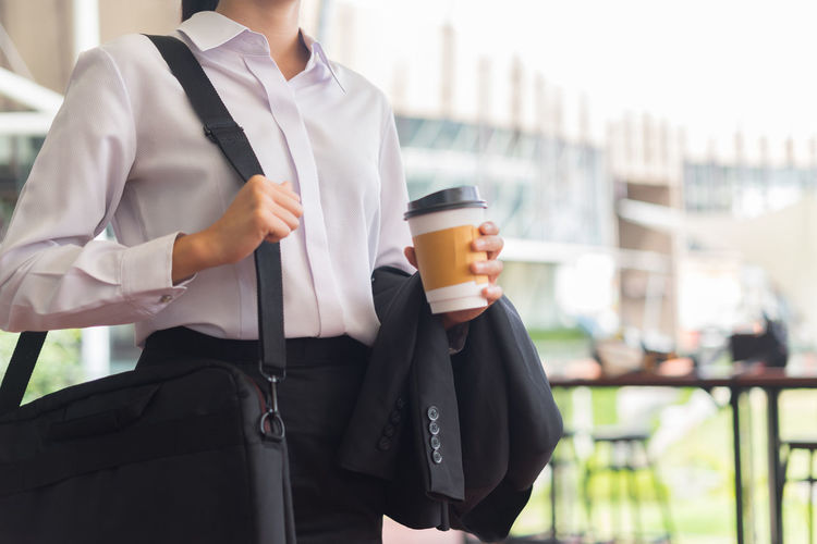 Midsection of businesswoman holding disposable cup