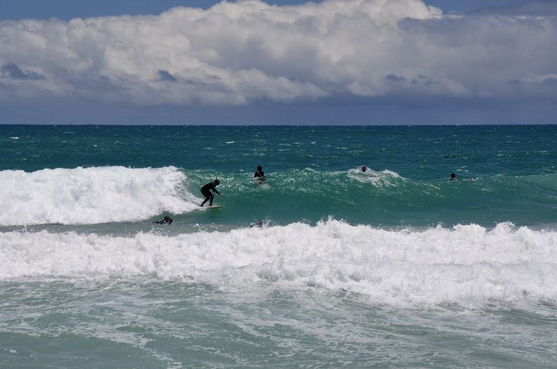Surfers in the turquoise indian ocean waves at scarborough beach in perth, australia