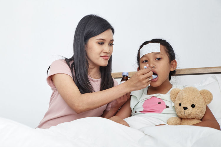 Mother giving syrup of ill daughter at home