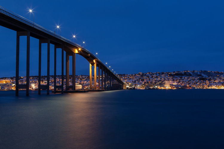Illuminated Tromso Bridge Over Tromsoysundet Strait At Night