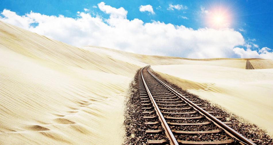 Railroad tracks in desert against sky